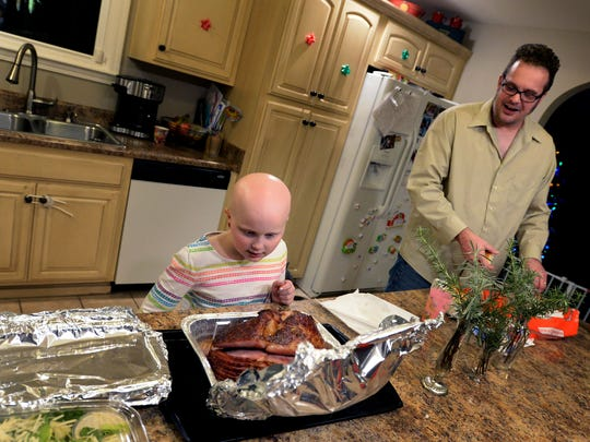 Rose Tavenner, 7, and her father Bernie get ready to eat dinner on Thursday, Dec. 14, 2017, in Nolensville, Tenn. Rose has alopecia, an auto-immune disease that causes hair loss. Mom and daughter now want to help others understand that beauty isn't just on the outside. It is about being bold, brave, confident and compassionate.