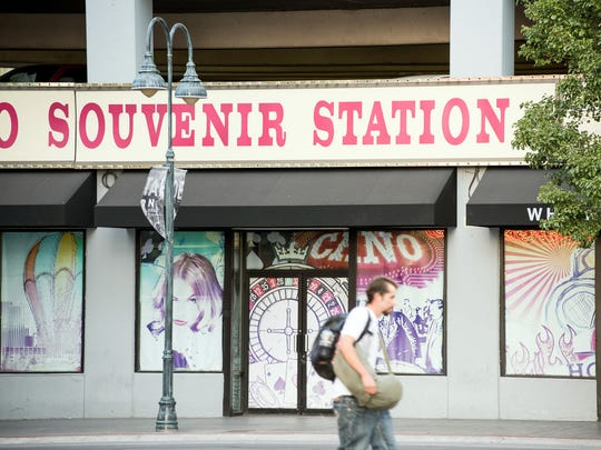 A closed souvenir shop uses vinyl murals to keep up