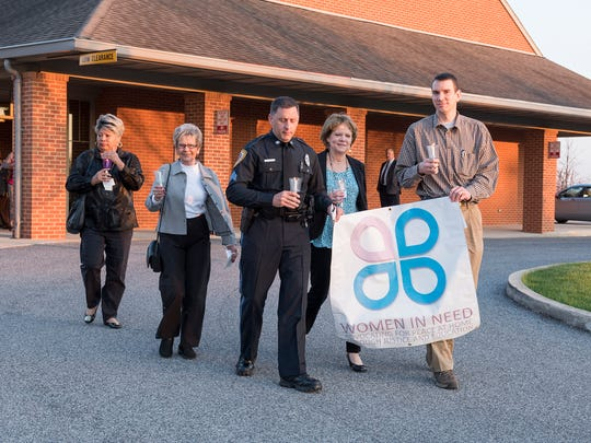 Community members walk together holding a sign during the candle light vigil walk during the 24th Annual Women in Need Vigil on Friday, April 15, 2016.