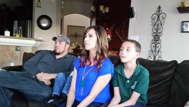 Anthony and Denise Ojinaga, with their sons Joshua, 3, and Jacob, 8, watch Pope Francis' mass at their home in Las Cruces Wednesday.