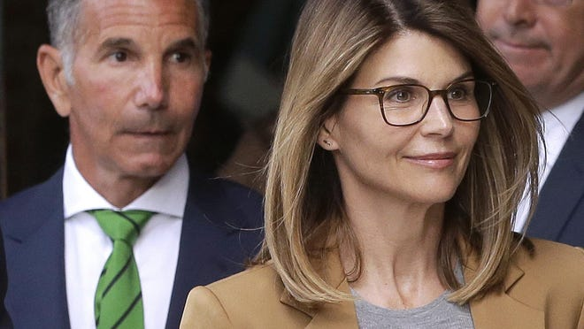 In this April 3, 2019 file photo, actress Lori Loughlin and husband, clothing designer Mossimo Giannulli, left, depart federal court in Boston. Loughlin and her husband Giannulli said in court documents Monday, April 15, 2019, that they are pleading not guilty to charges that they took part in a sweeping college admissions bribery scam.