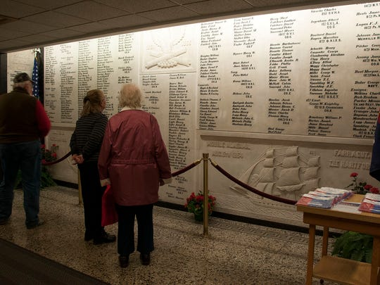 Visitors take in memorials to fallen Ottawa County servicemen in the lobby of the Ottawa County Courthouse in Port Clinton on Sunday.