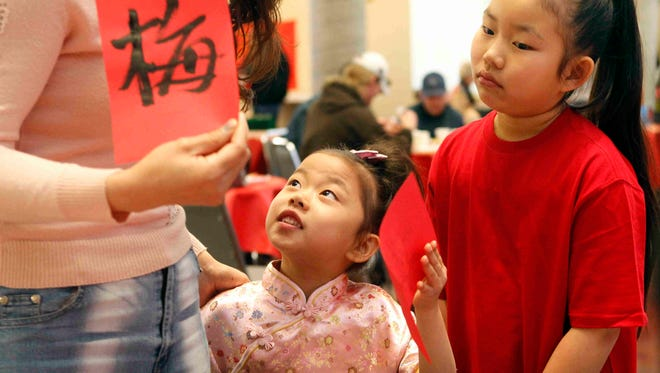 Jennifer Lin looks up to her mother after being handed her name in Chinese calligraphy during the San Angelo Museum of Fine Arts' Family Day-China in 2012.