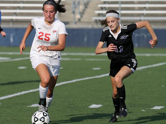 Canton's Hannah Lapko (left) maintains a step on Woodhaven's Nicole May.