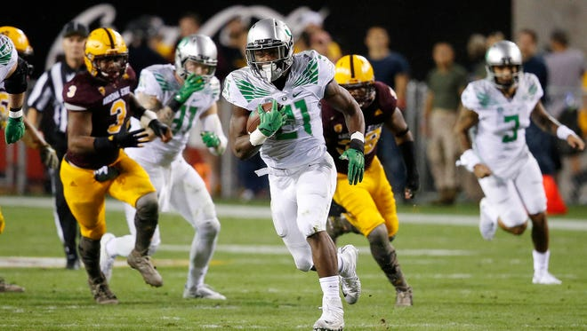 Oregon's Royce Freeman (21) gets past the Arizona State defense for a 64-yard touchdown run during the first half of an NCAA college football game Thursday, Oct. 29, 2015, in Tempe, Ariz.