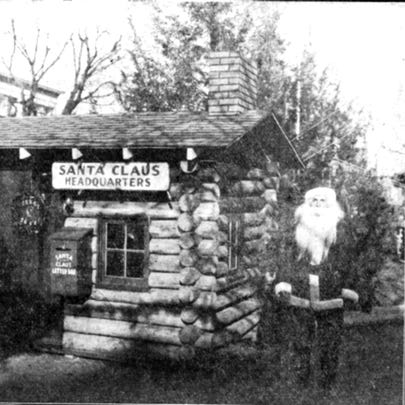 Santa stands in front of the first cabin constructed