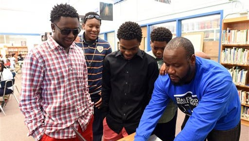 Dalewood Middle students Eric Kelly, Jamichael Wilson, Tahj Cargle and Jamaal Ward, from left, gather around a computer with teacher, Henry Oston, after performing a science rap song for 7th graders Wednesday, may 20, 2015,  at the school.  The four Dalewood Middle School students comprise the rap group Re-Generation, and on May 20 they were performing for the seventh-grade students at their end-of-the-year awards ceremony in the school's media center. The group has gained some fame of late, appearing on local radio and winning a regional competition at Chattanooga State Community College. (Angela Lewis Foster/Chattanooga Times Free Press via AP)