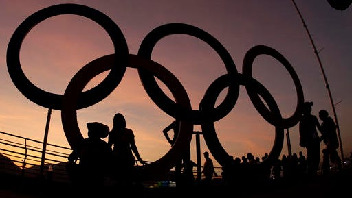 People pose in the Olympic rings at the Olympic Park during the 2016 Summer Olympics in Rio de Janeiro, Brazil.