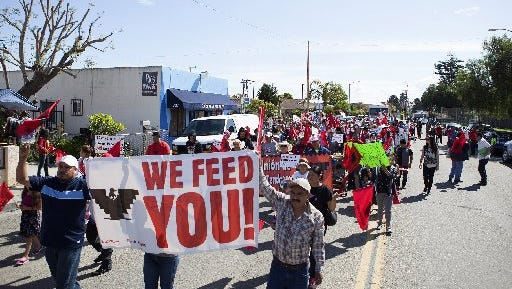 United Farm Workers, CAUSE, Ventura County farmworkers and community members march down Cooper Road in Oxnard in April. The demonstrators were marching in support of a state bill to extend overtime pay to farmworkers.