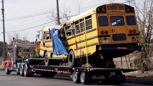 FILE- In this Nov. 22, 2016, file photo, a school bus is carried away in Chattanooga, Tenn., from the site where it crashed. Students and administrators raised concerns about a Tennessee school bus driver's behavior behind the wheel in the weeks before a crash that killed several children. Records released by the school district Friday, Nov. 25, include two written statements by students complaining about Johnthony Walker's driving.
