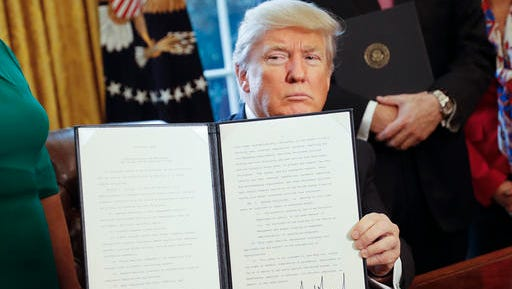 President Donald Trump holds up an executive order after his signing the order in the Oval Office of the White House in Washington, Friday, Feb. 3, 2017. The executive order that will direct the Treasury secretary to review the 2010 Dodd-Frank financial oversight law, which reshaped financial regulation after 2008-2009 crisis.