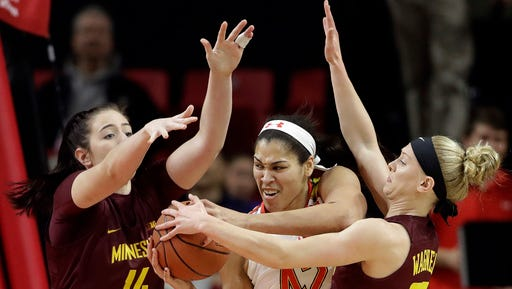 Maryland center Brionna Jones, center, drives between Minnesota center Bryanna Fernstrom, left, and guard Carlie Wagner in the first half of an NCAA college basketball game, Sunday, Feb. 26, in College Park, Md.