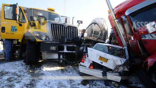 A car is wedged between a PennDOT truck and a tractor-trailer Friday after a weather-related crash on Interstate 81.