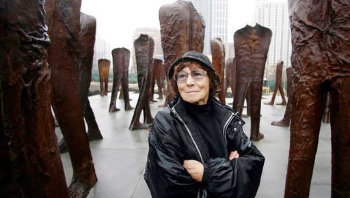 FILE - In this file photo taken Oct. 26, 2006, Polish sculptor Magdalena Abakanowicz stands before several of the 106 cast iron human figures, each nine feet tall, she created, as they were being installed in Chicago's Grant Park. Adam Myjak, the rector of Fine Arts Academy in Warsaw, Poland said on Friday, April 21, 2017, that Abakanowicz has died. She was 86-years-old.