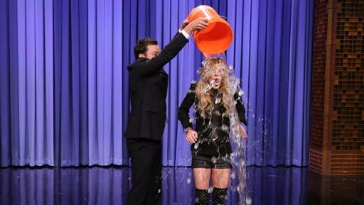 """NBC shows host Jimmy Fallon, left, dumping a bucket of ice water over the head of actress Lindsay Lohan as she participates in the ALS Ice Bucket Challenge on """"The Tonight Show Starring Jimmy Fallon,"""" in New York. The phenomenal success of the fundraising craze is making charitable organizations rethink how they connect with a younger generation of potential donors, specifically through social media."""