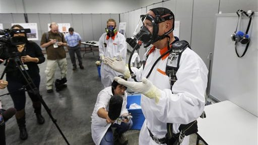 Bob Wilkinson, right, demonstrates protective and clothing and a scuba-type tank-and-mask breathing apparatus used by workers in areas with potential exposure to possibly harmful vapors of the Hanford Nuclear Reservation.