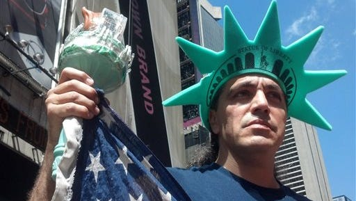 A man who calls himself Bonny Muneca, when working as a costumed Statue of Liberty on New York City?s Times Square, reveals his face after removing his mask, Tuesday, Aug. 19, 2014 in New York. He joined other costumed characters who work Times Square for tips at a news conference, where they proclaimed their right to make a modest living by posing for photos. Earlier in the month, the New York City Police Department started distributing leaflets and posting signs in five languages warning visitors that tips are optional. As a result, tip intake has plummeted. (AP Photo/Verena Dobnik)