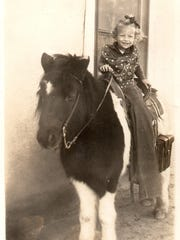 A small girl takes a pony ride in this vintage photo