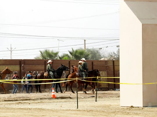 In this Oct. 19, 2017, file photo, a group of people are detained by Border Patrol agents on horseback after crossing the border illegally from Tijuana, Mexico, near prototypes for a border wall, right, being constructed in San Diego.