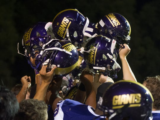 Waynesboro players lift their helmets in the air before leaving the field after being beaten by Riverheads on Friday, Sept. 19, 2014.