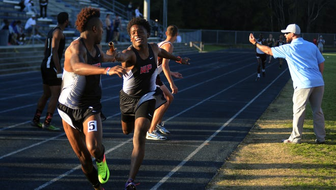 West Florida Tech's Damond Johnson (left) receives the baton from Keyshawn Helton in the Jaguars' 4x400 win at the Panhandle Championships on Feb. 25, 2017.