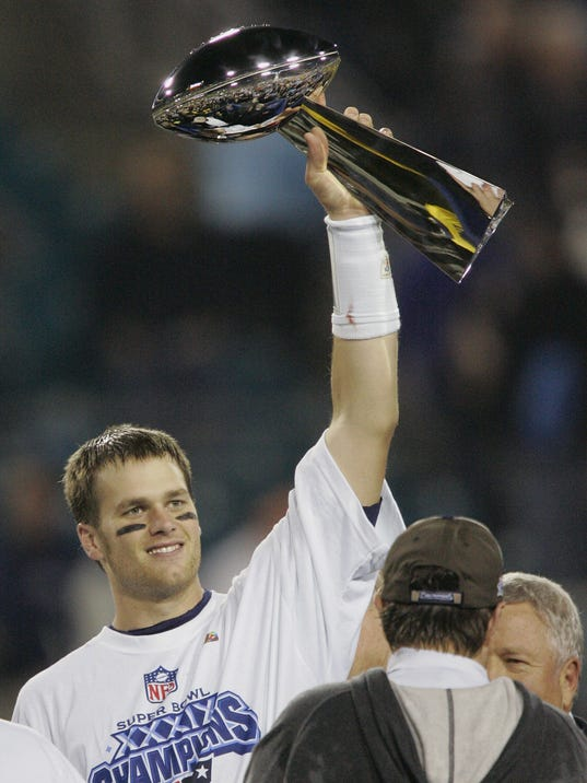FILE - In this Feb. 6, 2005, file photo, New England Patriots quarterback Tom Brady raises the Vince Lombardi Trophy over coach Bill Belichick and team owner Robert Kraft, right, after they beat the Philadelphia Eagles, 24-21, in Super Bowl XXXIX in Jacksonville, Fla. The two teams meet in a rematch in Super Bowl 52 on Sunday, Feb. 4, 2018, in Minneapolis. (AP Photo/Julie Jacobson, File)