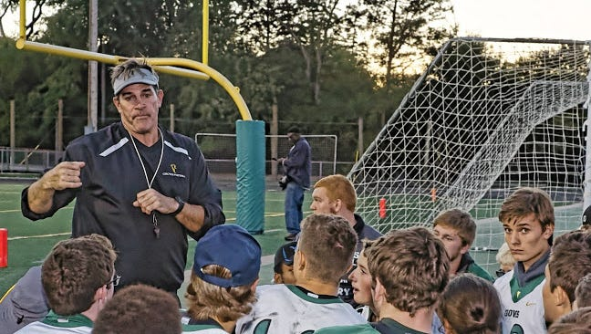 Birmingham Groves football head coach Brendan Flaherty talks to Groves and Seaholm players about 2016 Victory Day proceedings at Birmingham Groves High School.