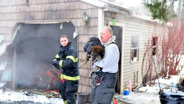 Seaford Fire Departments firefighter Jack Wilson carries a dog that was rescued from an early morning garage fire on Lonesome Rd in Seaford De. The crew of Engine 87-2 found the dog inside while battling the fire. The 11yr old dog was transported via Seaford's Rescue truck to a local vet for treatment with burns to his nose, face and ears. Wayne Barrall photo.