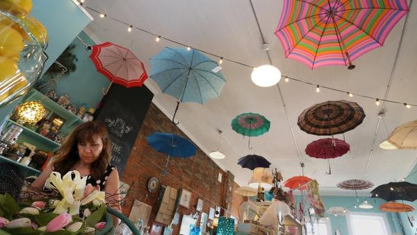 Barb Mueller, owner of My Oh My! Boutique works on converting wreaths made of garden hose to a summer look rather than their current spring look, Thursday, July 2, 2015, at the shop in Marshfield. Umbrellas hang from the ceiling throughout the shop.