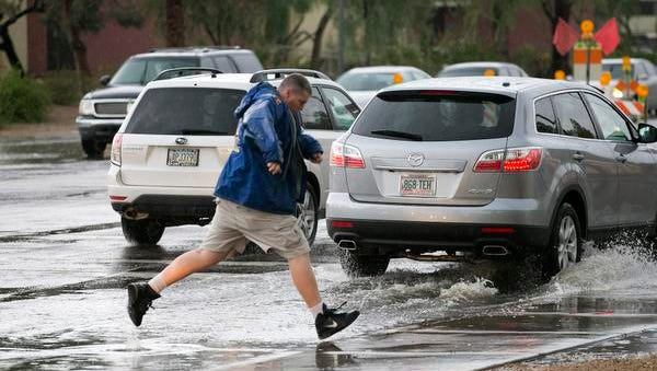 Jeff Emery of Tempe jumps over a pool of water across Southern Avenue during heavy rains in Mesa on Thursday, August 27, 2015.