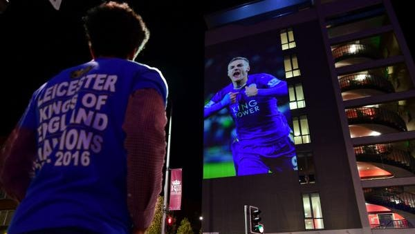 A Leicester City football fan looks up at a large projection of an image of Leicester City's striker Jamie Vardy on the side of a building as the city celebrate's their team becoming the English Premier League champions in central Leicester, eastern England, on May 2, 2016. Leicester City completed their fairytale quest for the Premier League title on May 2 after Eden Hazard's stunning late goal earned Chelsea a 2-2 draw with second-place Tottenham Hotspur.