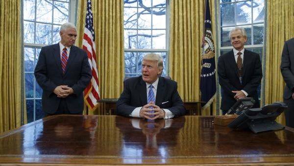 Vice President Mike Pence, left, and National Trade Council adviser Peter Navarro, right, wait for President Donald Trump to sign three executive orders, Monday, Jan. 23, 2017, in the Oval Office of the White House in Washington. (AP Photo/Evan Vucci)