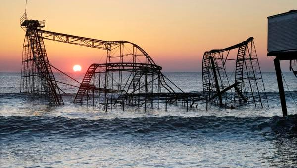 In this Feb. 25, 2013, file photo, the sun rises behind the Jet Star roller coaster, partially submerged in the Atlantic Ocean after Superstorm Sandy destroyed part of the Casino Pier in Seaside Heights. A new roller coaster named Hydrus, built safely inland above the beach rather than out over the water, opened May 6, 2017, more than four years after the storm caused billions of dollars' worth of damage to the coast.