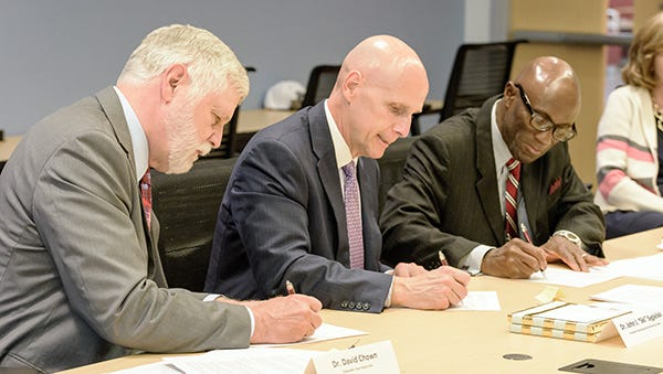"""From left: Penn State York Chancellor David Chown, HACC President John J. """"Ski"""" Sygielski, and Penn State Mont Alto Chancellor Francis K. Achampong sign articulation agreements allowing graduates with a HACC associate degree to enroll in a parallel Penn State Mont Alto or Penn State York program."""