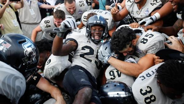 UCF Knights defensive back Kyle Gibson (25) celebrates with teammates after beating the Memphis Tigers in double overtime at Spectrum Stadium.