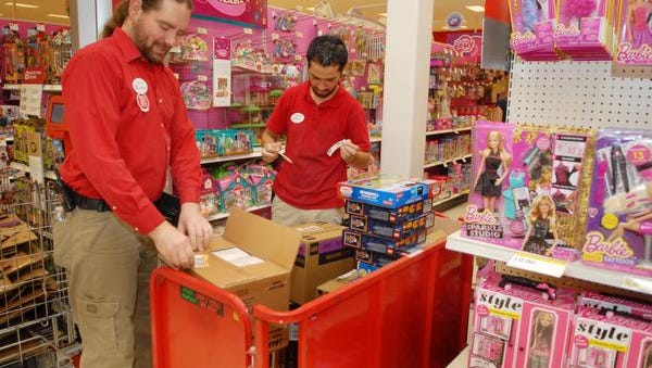 Patrick Higgins and Ross Ghassen unpacking boxes and stocking toys shelves at the SuperTarget in Viera. They are members of the sales and service team, but are not temporary holiday season staff.