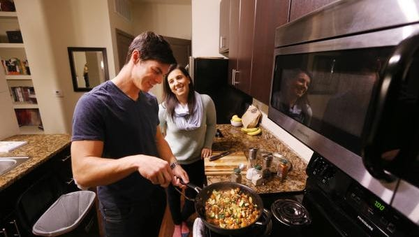 Indianapolis Colts receiver Griff Whalen cooks up a vegetarian dish with his girlfriend, Katie Osadetz, at their downtown apartment on Wednesday, October 29, 2014. Whalen works with a plant-based diet that he feels is helping him play better as a Colt.