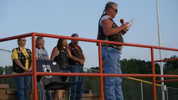 Phil Dennison, president of Rolling Thunder Chapter 5 in Mount Gilead, dedicates the POW empty chair at Arlin Field on Friday night. The chair is dedicated in honor of prisoners of war and soldiers still missing in action.
