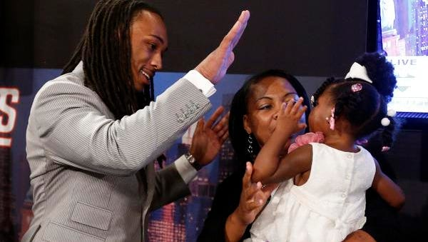 Calvin Pryor, from Louisville, high-fives with his 2-year-old daughter Jayle Exum and mother Monique Turrell after being selected 18th overall by the New York Jets in the first round of the NFL football draft, Thursday, May 8, 2014, at Radio City Music Hall in New York.