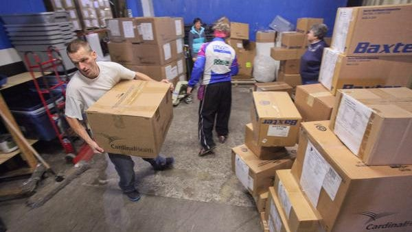 Michael Ludwig, left, carries a box onto a shipping container with other medical supplies and equipment bound for Syrian refugees in Beirut, Lebanon, sponsored by the Muslim Mercy Foundation and the Sisters of Charity of Nazareth, at the Supplies Over Seas warehouse.