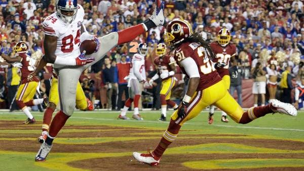 Giants tight end Larry Donnell (84) pulls in his second touchdown of the game under pressure from Washington strong safety Brandon Meriweather (31) during the first half Thursday night in Landover, Md.