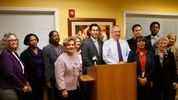 Michael Mandel, center, without jacket, executive director for the Center for Safety and Change in New City, with local elected officials after a press conference recognizing National Domestic Violence Awareness and the 35th anniversary of the center on Oct. 16, 2014.