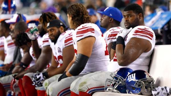 Giants defensive tackle Johnathan Hankins, right, sits on the bench with teammates during the second half against the Eagles Sunday night in Philadelphia.