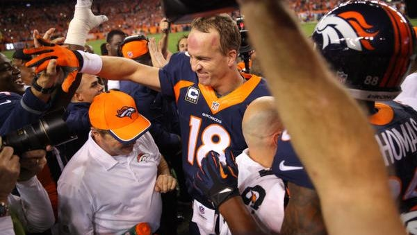 Quarterback Peyton Manning of the Denver Broncos celebrates with teammates and the coaching staff on the sideline after throwing his NFL-record 509th career touchdown pass Sunday night.