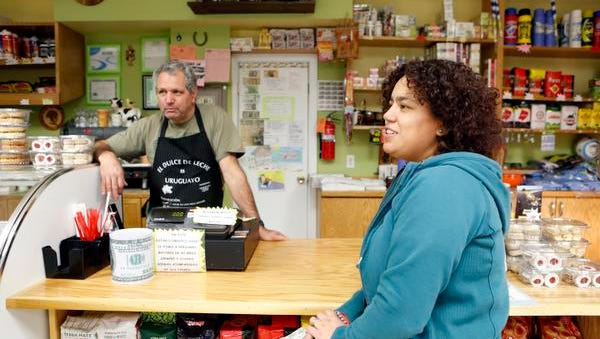 Noroselly Peerez, owner of Cafe Zitarrosa, and customer Jhiannina Gonzales of Stamford, Conn. discuss President Obama's immigration plan, Nov. 22, 2014 in Port Chester.