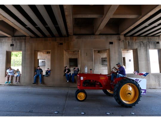 A tractor goes under the Pine Street underpass during the Western Heritage Classic parade Thursday. During the parade a motorcycle group going north on the route spooked a carriage going south, returning to the parade staging area near this underpass. The carriage driver was injured, but passengers state Sen. Dawn Buckingham and her aide were not.