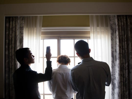 Students with the inaugural Corporate Development Program with Taste of Immokalee take photos out of an executive suite window during a tour of the Ritz-Carlton, Naples on Thursday, Aug. 3, 2017.