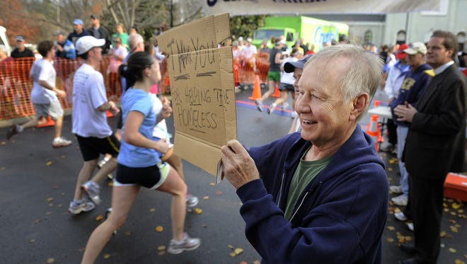 Homeless advocate Charles Strobel, right, holds a sign thanking thousands of runners for participating in the Boulevard Bolt Thanksgiving morning on Nov. 25, 2010. The event raised money for 22 area charities, including Strobel's Room in the Inn.