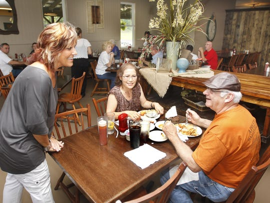 Cindy Ellis talks with longtime customers Lee and Jim