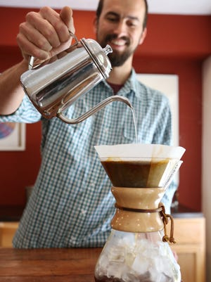 Les Stoneham makes an iced chemex at Deeper Roots Coffee, a coffee roaster in Mount Healthy.